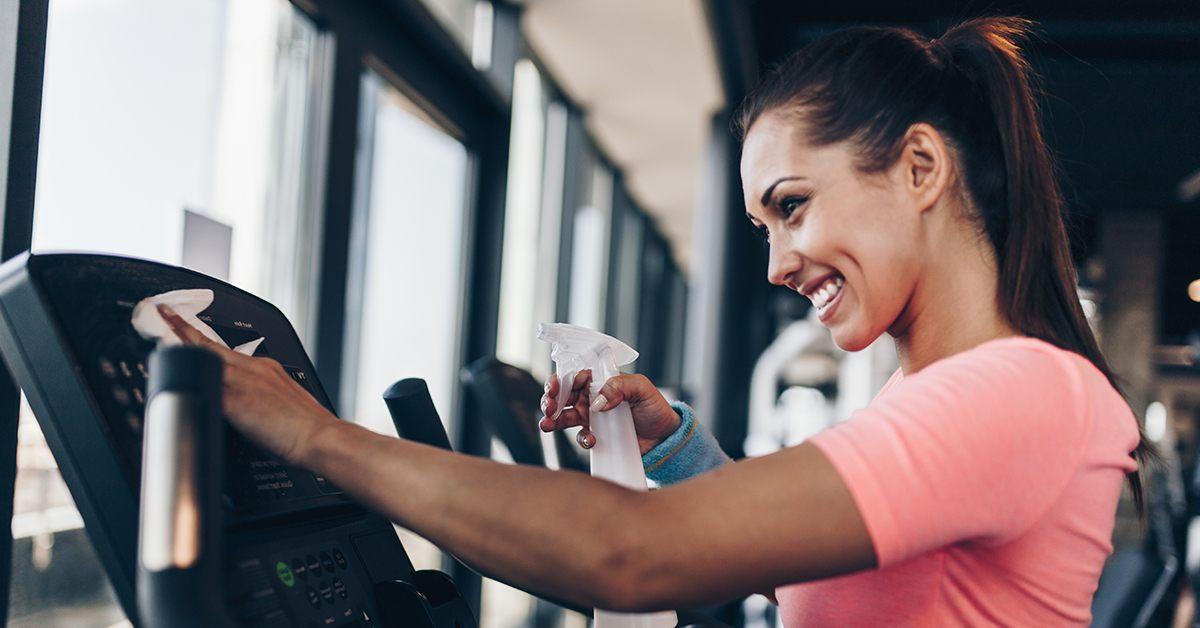 Fitness woman cleaning gym coronavirus